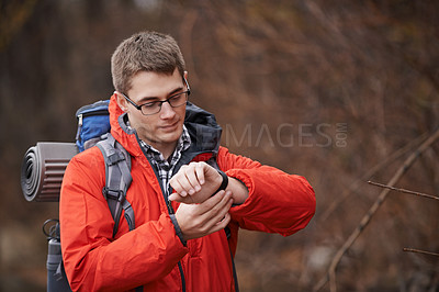 Buy stock photo Cropped shot of a hiker looking at his wristwatch