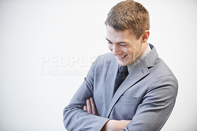 Buy stock photo Studio shot of a young businessman laughing with his arms folded against a grey background