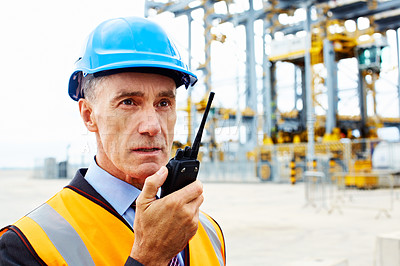 Buy stock photo Shot of a man in workwear standing outside on a large commercial dock talking on a walkie talkie