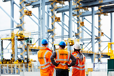 Buy stock photo Rearview shot of of three dock workers looking up at loading cranes