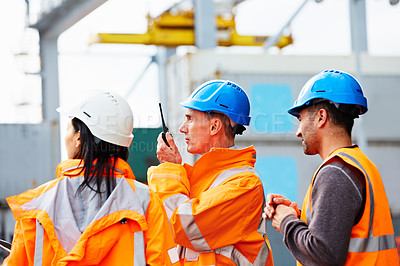 Buy stock photo Shot of three workers standing on a commercial dock