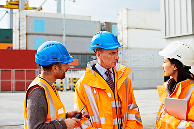 Buy stock photo Shot of three workers talking together while standing on a commercial dock