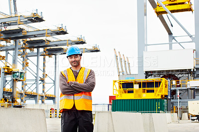 Buy stock photo Portrait of a young man in workwear standing outside on a large commercial dock