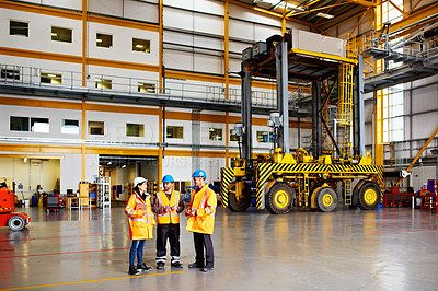 Buy stock photo Shot of three workers standing in a large commercial warehouse
