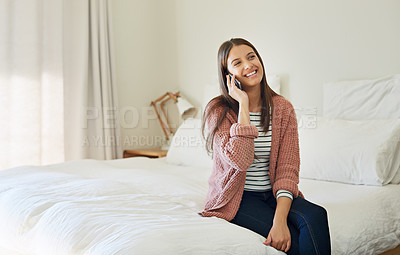 Buy stock photo Shot of a young woman sitting on her bed talking on a cellphone