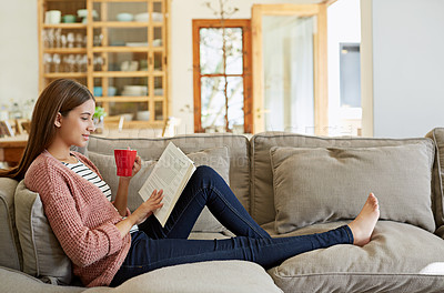 Buy stock photo Shot of a young woman sitting on her sofa reading a book and drinking a coffee