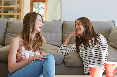 Buy stock photo Shot of two female friends sitting on the living room floor talking together
