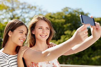 Buy stock photo Shot of two friends taking a selfie together while standing outside
