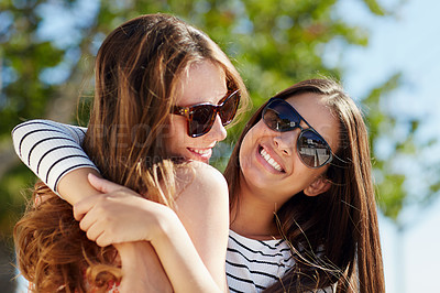Buy stock photo Portrait of two young friends hugging while enjoying a day outside together