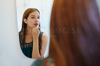 Buy stock photo Shot of a young woman putting on lipstick in her bathroom mirror