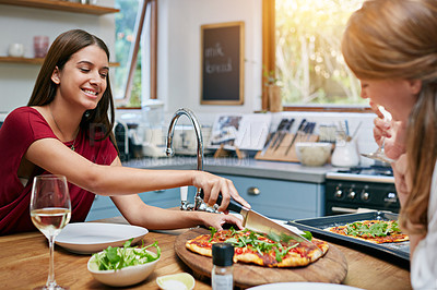Buy stock photo Shot of two friends sitting at the kitchen table eating pizza and drinking wine