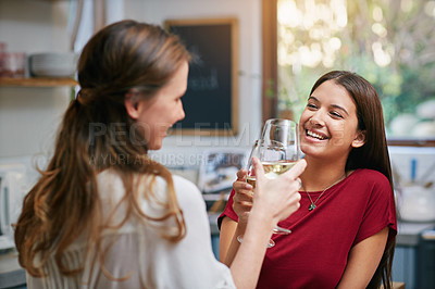 Buy stock photo Shot of two friends standing in a kitchen drinking wine together