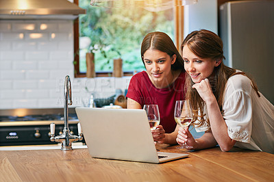 Buy stock photo Shot of two friends sitting at the kitchen table using a laptop and drinking wine