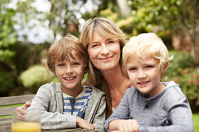Buy stock photo Portrait of a grandmother hugging her grandsons while sitting at a table in her yard