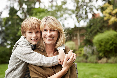Buy stock photo Portrait of a grandmother and her young grandson hugging outside