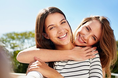 Buy stock photo Shot of two young friends hugging while talking a selfie outside together