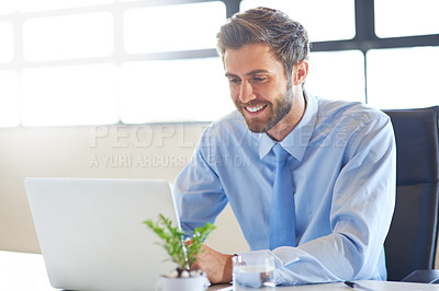 Buy stock photo Shot of a young businessman using a laptop in an office