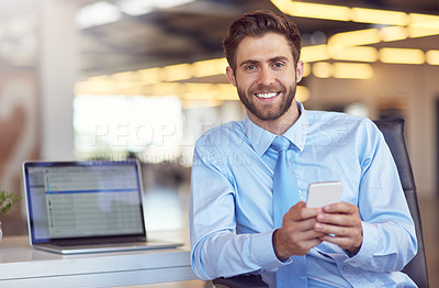 Buy stock photo Portrait of a young businessman using his phone in the office