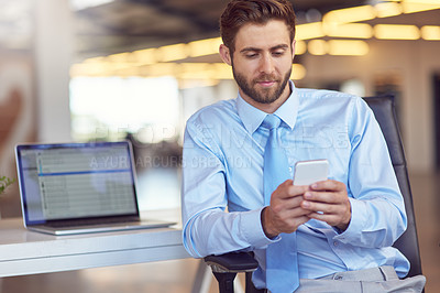 Buy stock photo Shot of a young businessman using his phone in the office