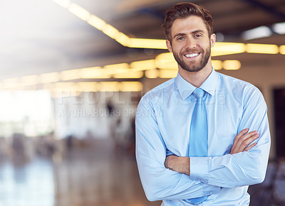 Buy stock photo Portrait of an ambitious young businessman standing with his arms folded in an office