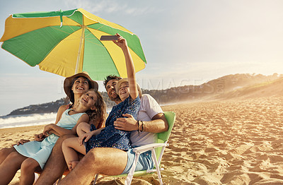 Buy stock photo Shot of a young girl taking a selfie with her family at the beach