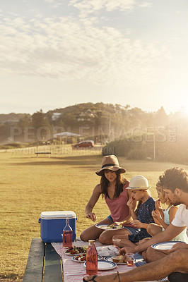 Buy stock photo Shot of a young family having lunch while out on a picnic