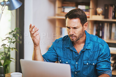 Buy stock photo Cropped shot of a businessman looking a little frustrated while working at home