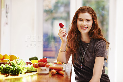 Buy stock photo Portrait of a young woman eating fresh strawberries at home