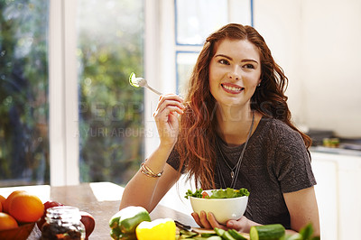 Buy stock photo Shot of a young woman eating a healthy salad at home