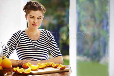 Buy stock photo Portrait of a young woman eating freshly cut oranges at home