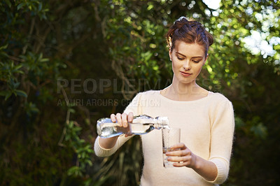 Buy stock photo Shot of a young woman pouring a glass of water outdoors