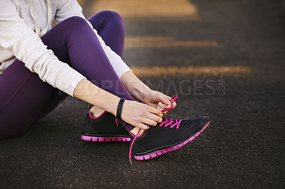 Buy stock photo Cropped shot of a young woman tying her laces before starting her early morning run