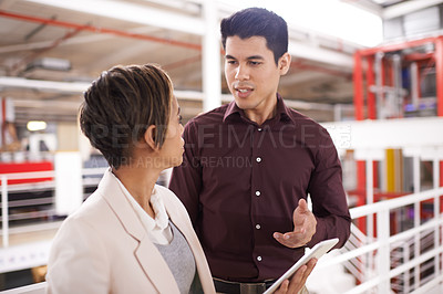 Buy stock photo Cropped shot of two young colleagues talking in the hallway