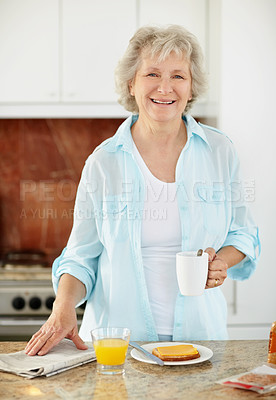Buy stock photo Portrait of a senior woman holding a cup of coffee while having breakfast