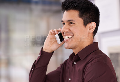 Buy stock photo Shot of a young businessman using a mobile phone in an office