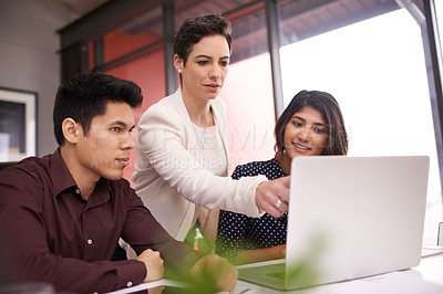 Buy stock photo Cropped shot of a mature businesswoman supervising the work of two young employees