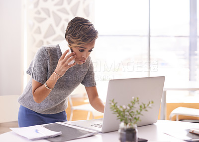 Buy stock photo Shot of a businesswoman talking on her cellphone while looking at her laptop screen
