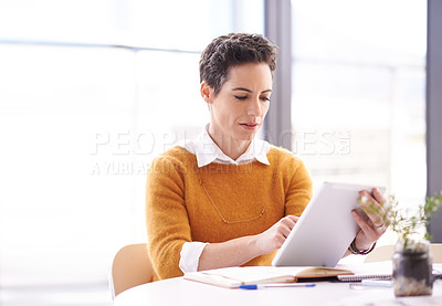 Buy stock photo Shot of a businesswoman using her tablet at her desk