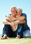 Senior couple sitting on grass and smiling