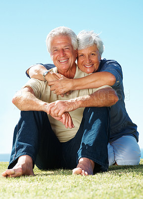 Buy stock photo Full length of senior couple sitting on grass and smiling with woman embracing man from behind