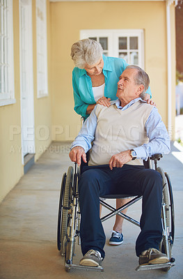 Buy stock photo Shot of a senior woman pushing her husband in a wheelchair at a retirement home