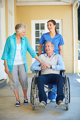 Buy stock photo Shot of a doctor standing with her senior patient and his wife