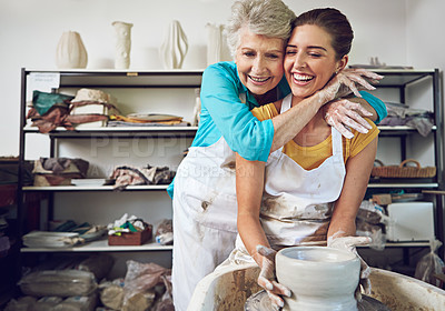 Buy stock photo Shot of a mother and daughter making a ceramic pot together in a workshop