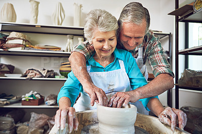 Buy stock photo Shot of a senior couple making a ceramic pot together in a workshop