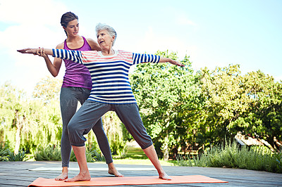 Buy stock photo Shot of a senior woman doing yoga with her instructor