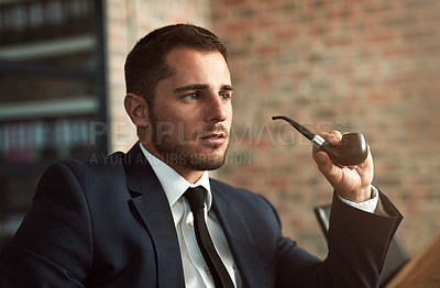 Buy stock photo Shot of a stylish businessman smoking a pipe in the office