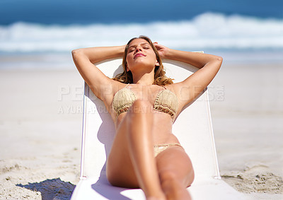 Buy stock photo Cropped shot of a young woman relaxing at the beach