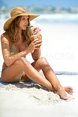 Buy stock photo Full length shot of a young woman drinking from a coconut while relaxing at the beach