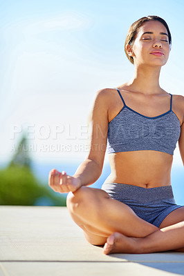 Buy stock photo Cropped shot of a young woman doing yoga outdoors