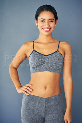 Buy stock photo Shot of a sporty young woman posing against a grey background